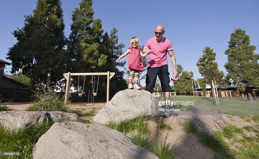 Father and daughter exploring in a public park : Stock Photo