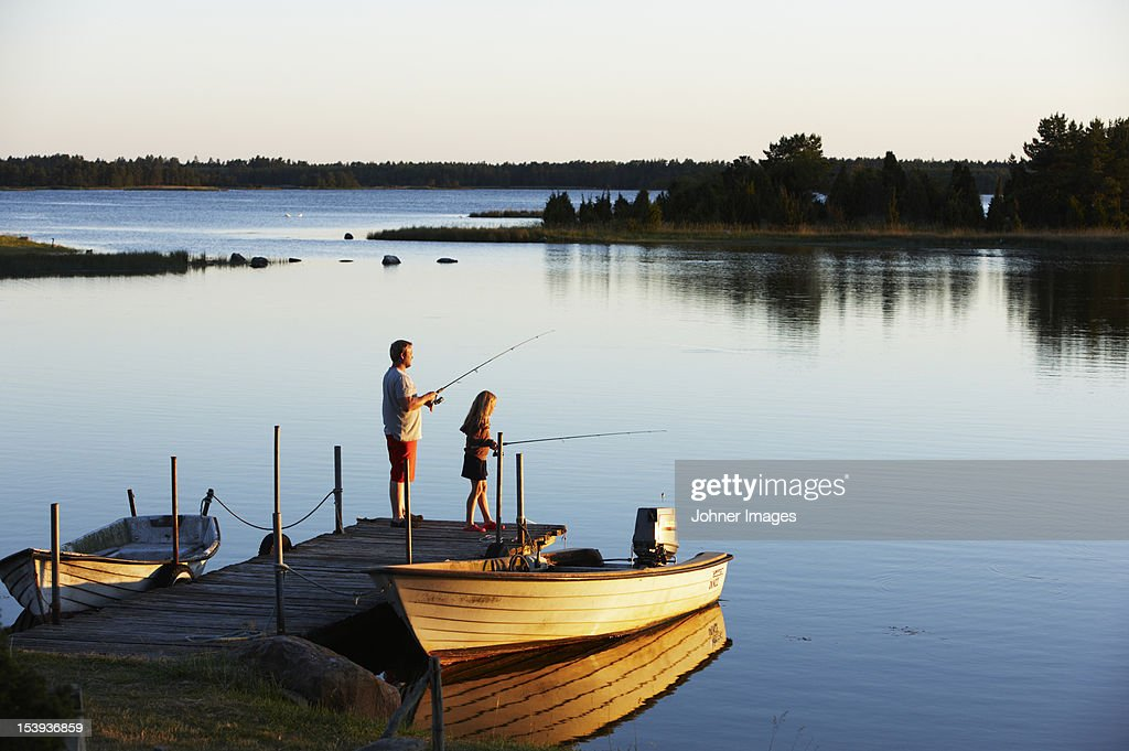 Father and daughter fishing from a jetty, Sweden.