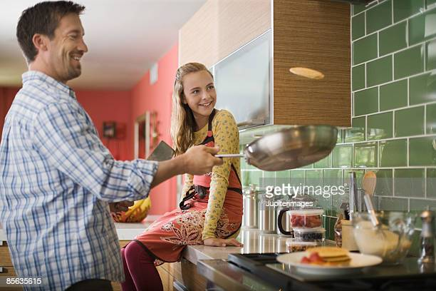 Father and daughter flipping pancakes