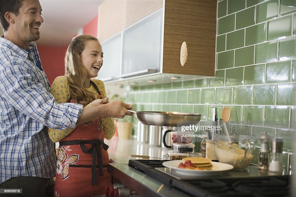 Father and daughter flipping pancakes : Stock Photo