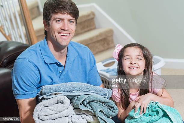Father and daughter folding laundry