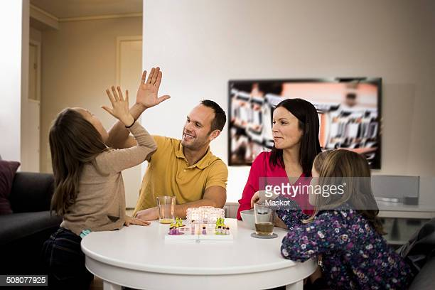 Father and daughter giving high-five while playing ludo at coffee table