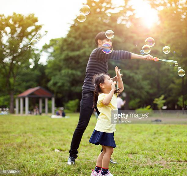 Father and daughter having fun in park with Soap Bubbles