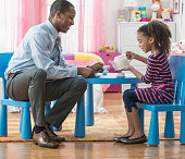 Father and daughter having tea party in playroom