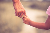 Father and daughter holding hand together in vintage color tone
