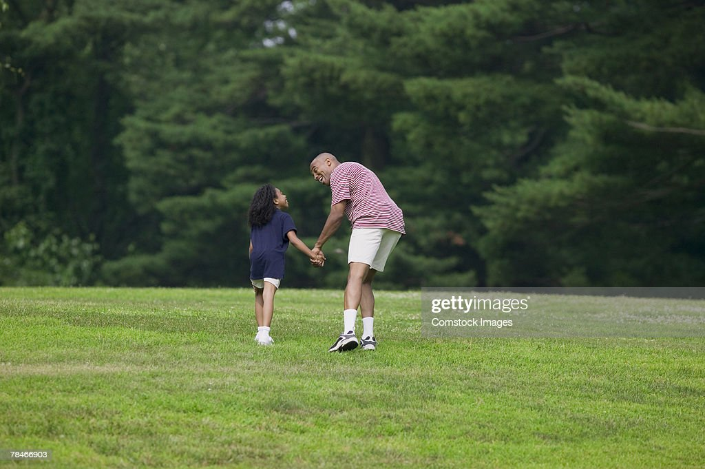 Father and daughter holding hands and walking in grass meadow : Stock Photo