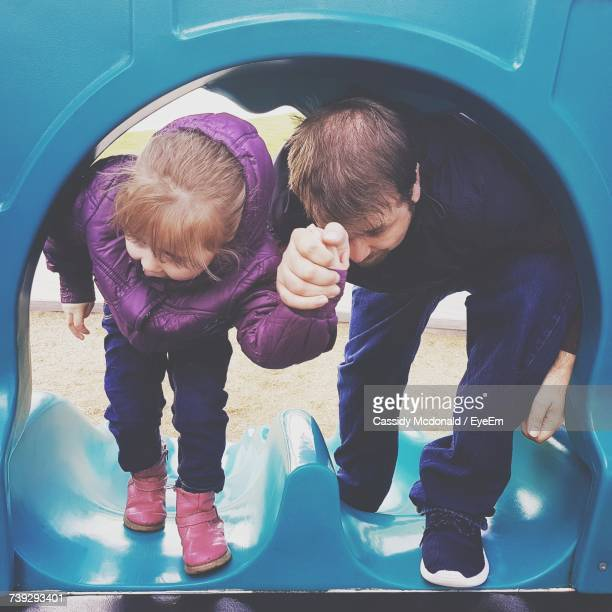 Father And Daughter Holding Hands In Outdoor Play Equipment At Playground