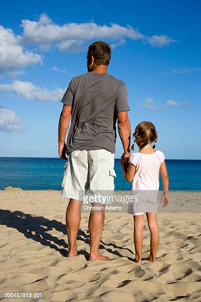Father and daughter (4-6) holding hands on beach, rear view