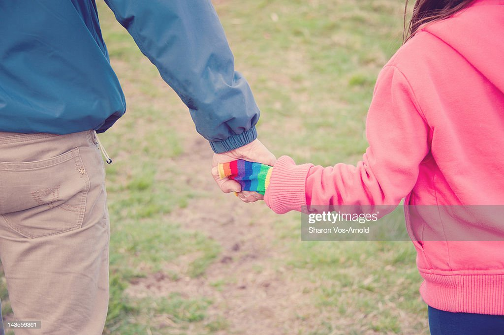 Father and daughter holding hands, walking : Stock Photo