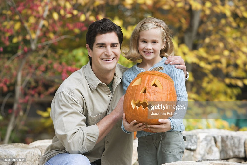 Father and daughter (6-7) holding jack o'lantern : Stock Photo