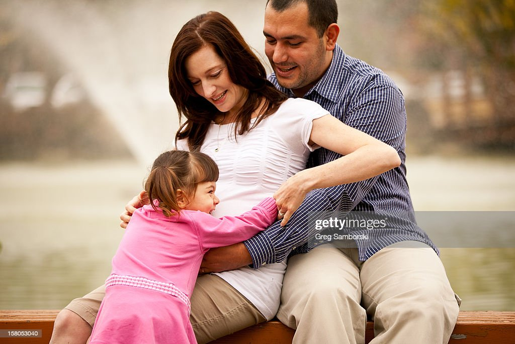 Father and Daughter Hugging Pregnant Mother : Stock Photo