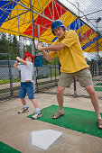 Father and daughter in batting cage