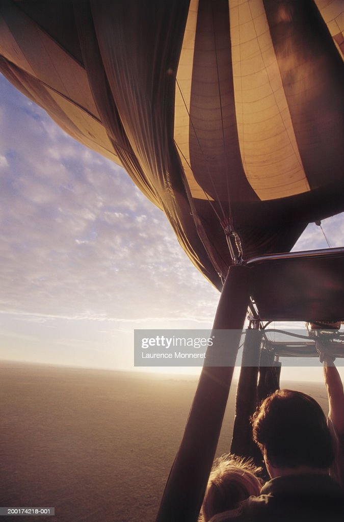 Father and daughter (6-8) in hot air balloon, sunrise : Stock Photo