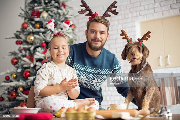 Père et fille à la cuisine pour Noël avec leur chien.