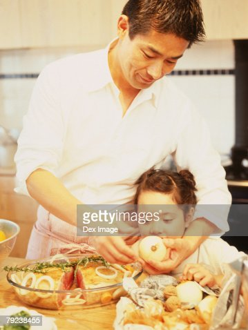 Father and daughter in kitchen preparing food : Stock Photo