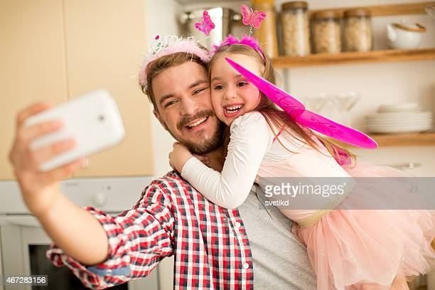 Father and daughter in kitchen taking selfies.