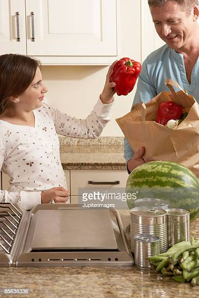 Father and daughter in kitchen with groceries