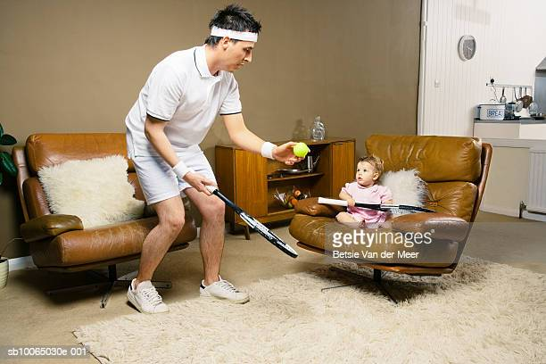Father and daughter (9-12 months) in living room, holding tennis racquet
