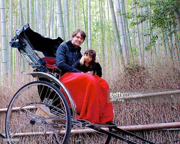 Father and daughter in rickshaw in bamboo forest