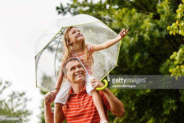 Padre e figlia sotto la pioggia.