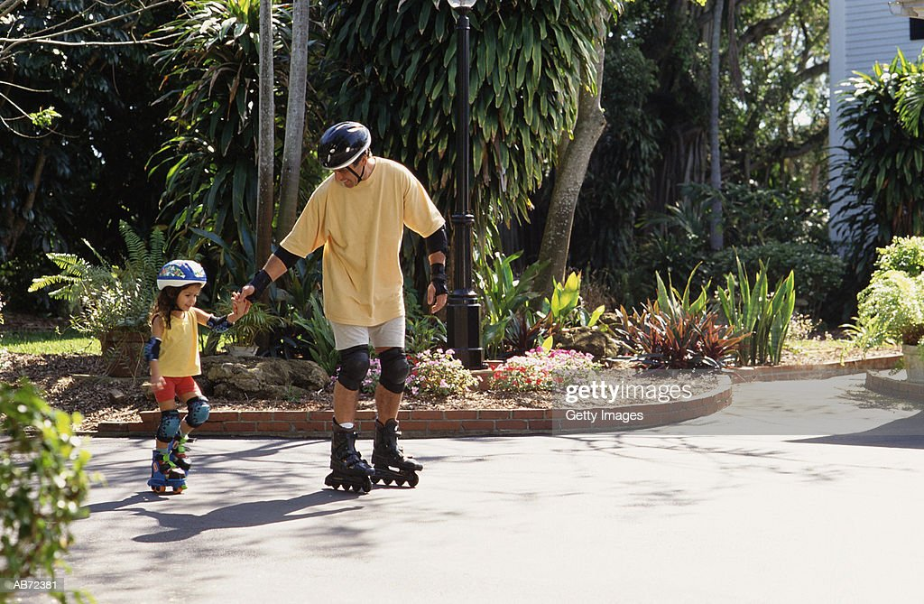 Father and daughter (4-6) in-line skating : Stock Photo