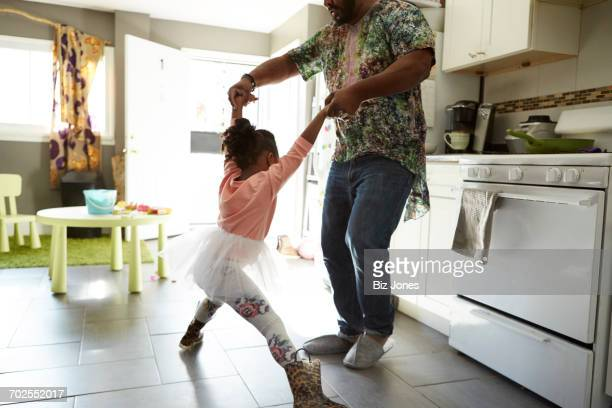 Father and daughter jiving in kitchen