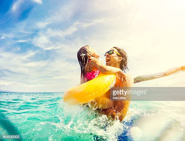 Father and daughter jumping and having fun together in sea