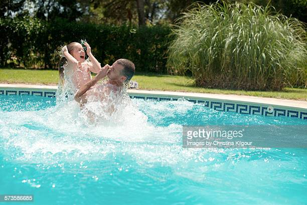 Father and daughter jumping in a pool