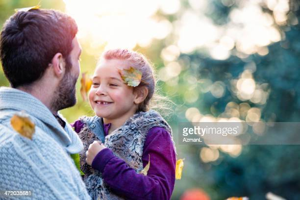 Father and daughter laughing in outdoor autumn setting