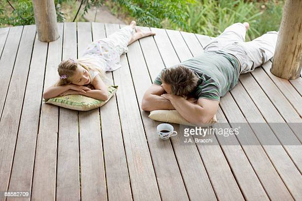 Father and daughter laying on porch