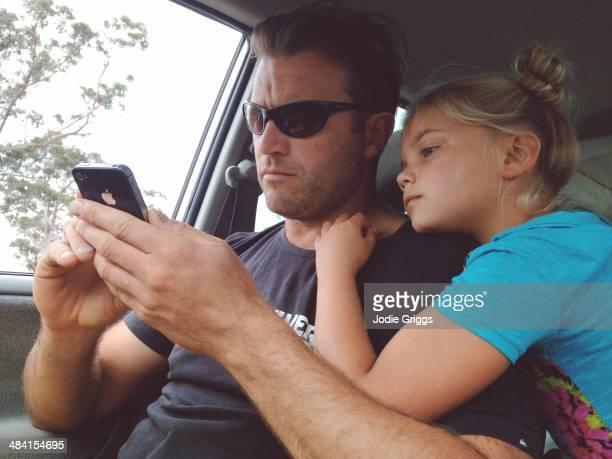 Father and daughter looking at a smart phone while waiting in a car