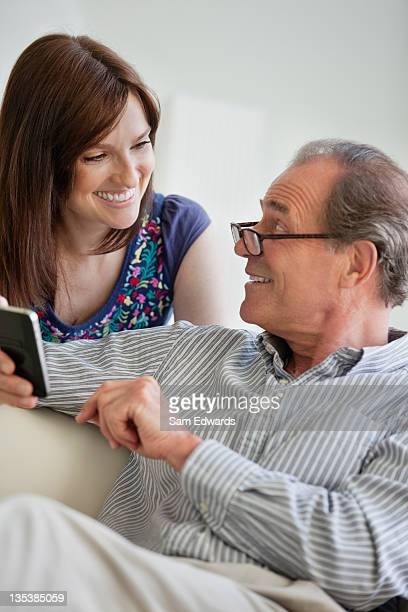 Father and daughter looking at cell phone