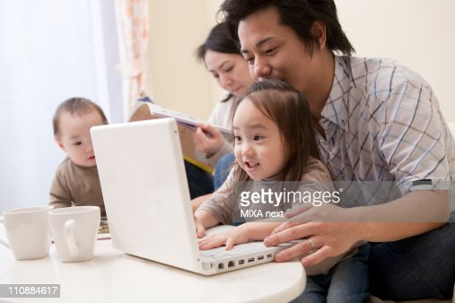 Father and Daughter Looking at PC : Stock Photo