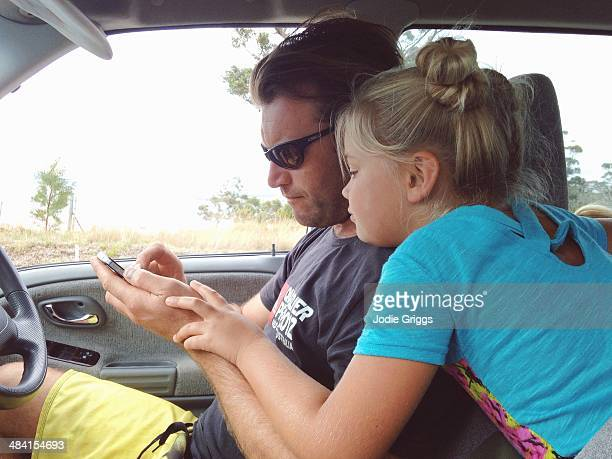 Father and daughter looking at smart phone while waiting in the car