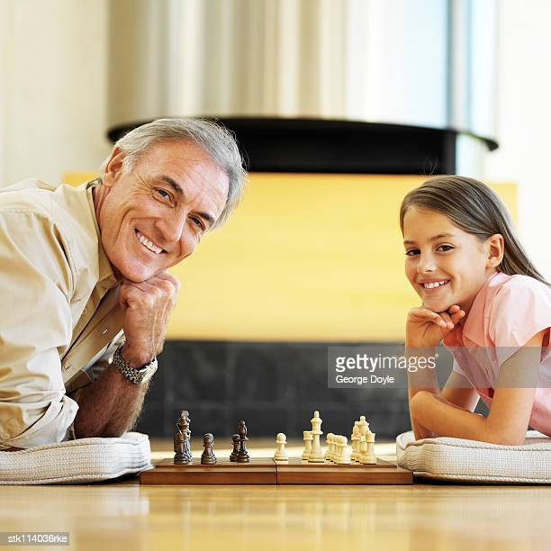 father and daughter lying on the floor playing chess