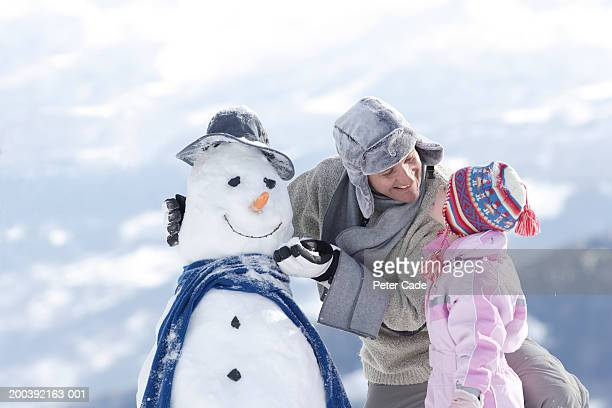 Father and daughter (3-5) making a snowman, side view, close-up
