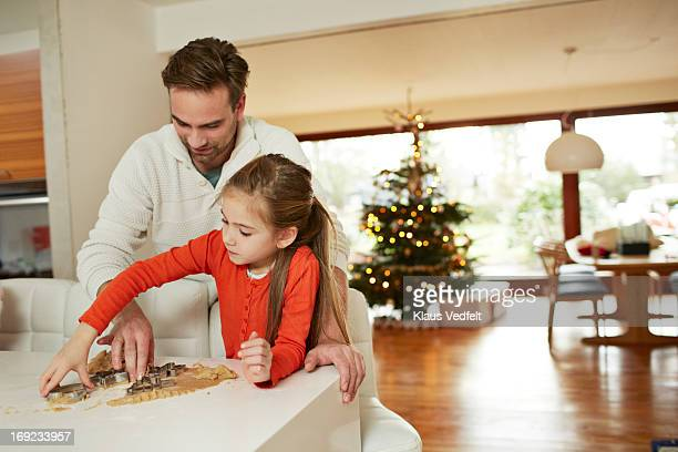 Father and daughter making christmas cakes
