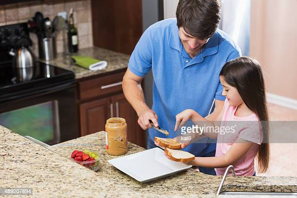 Father and daughter making peanut butter sandwich