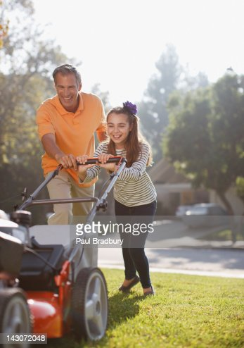 Father and daughter mowing lawn together : Stock Photo