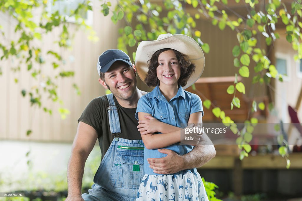 Father and daughter on family farm smiling at camera : Stock Photo