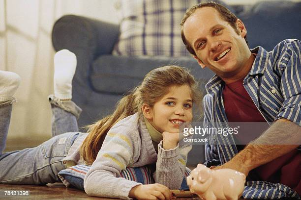 Father and daughter on floor with piggy bank