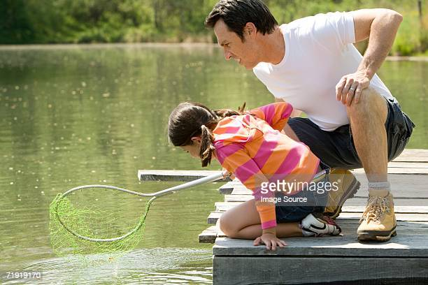 Father and daughter on jetty, holding fishing net