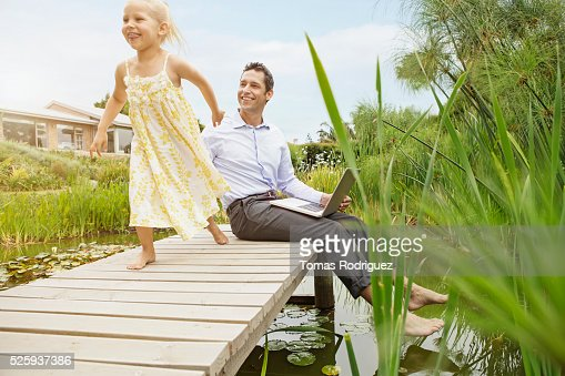 Father and daughter (4-5) on jetty : Stock Photo