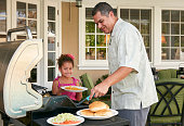 Father and daughter on patio grilling barbecue food smiling