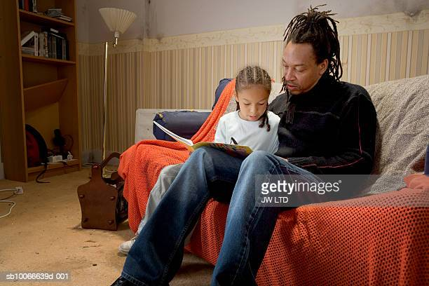 Father and daughter on sofa with book