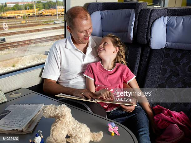 Father and daughter on train