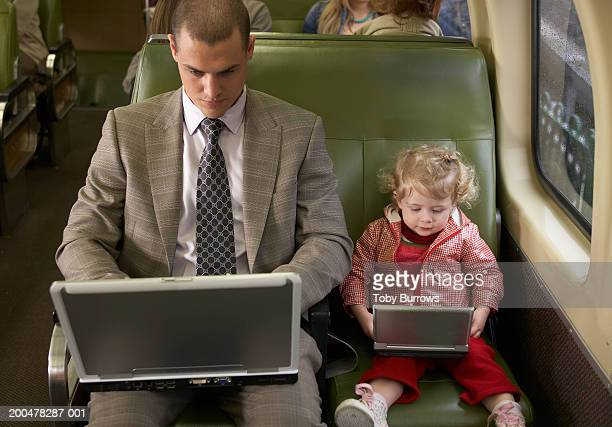 Father and daughter (1-3) on train using laptop and DVD player