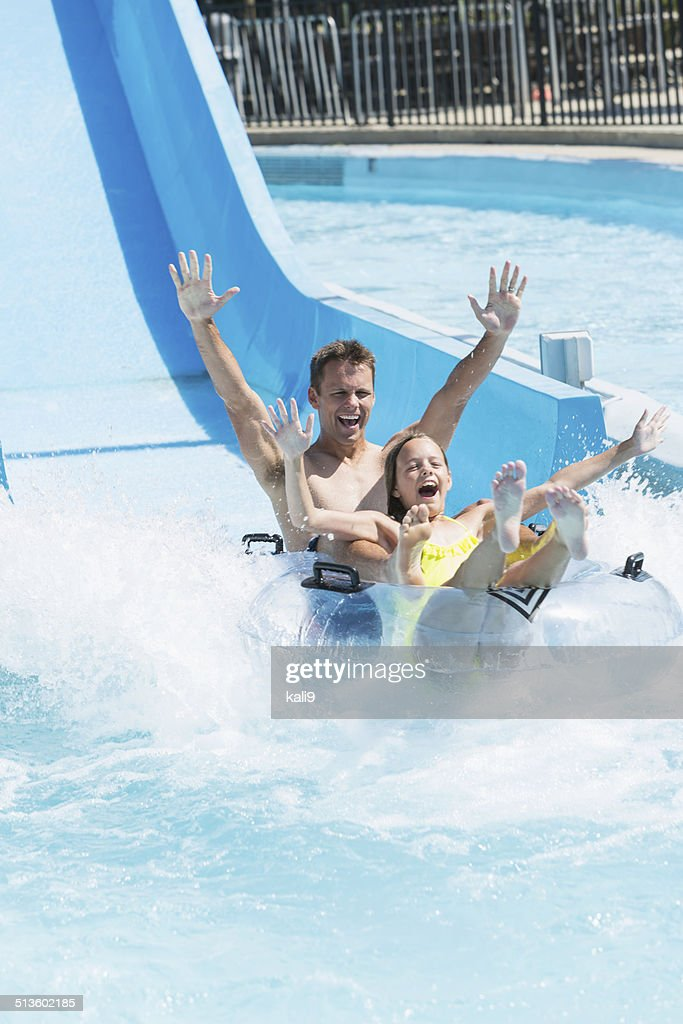 Father and daughter on water slide : Stock Photo