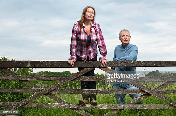 Father and daughter on wooden fence