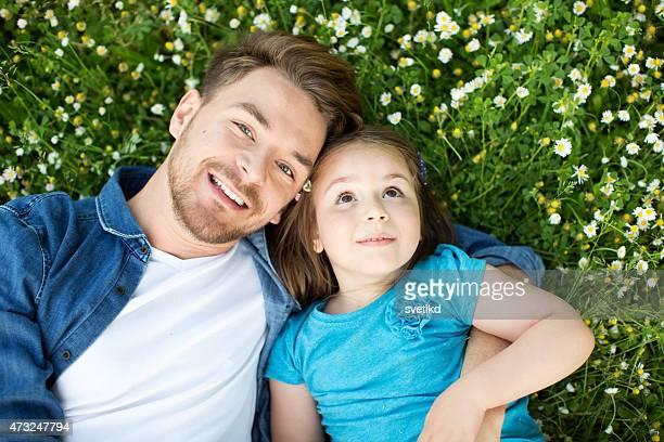 Père et fille en plein air dans une prairie.